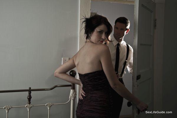 Woman in evening gown, man at door