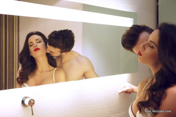 Sexy man kissing woman neck at mirror in bathroom, passionate couple
