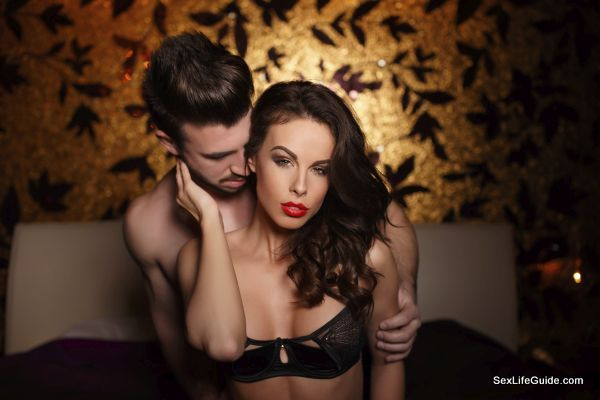 Passionate lovers in bed foreplay