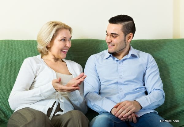 Young man and aged woman talking indoor